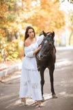 女孩走与一匹马在autmn公园并且看她 库存图片