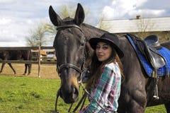 女孩走与一匹黑马本质上 免版税库存图片