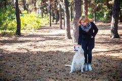 女孩走与一条狗在公园 免版税库存照片