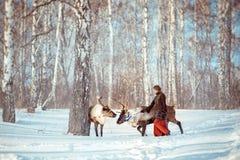 女孩走与一头驯鹿在冬天 免版税库存图片