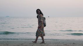 女孩走与在海洋的一个背包 股票视频