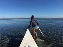 女孩走与在筏小船前面的低潮 图库摄影