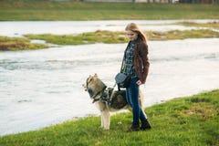 女孩走与沿堤防的一条狗 美丽的多壳的狗 海岸冰横向河水冬天 春天 库存照片