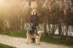 女孩走与沿堤防的一条狗 美丽的多壳的狗 海岸冰横向河水冬天 春天 库存图片
