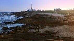 女孩走沿海靠近灯塔在日落 股票视频