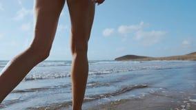 女孩走海滩和在水中 股票录像