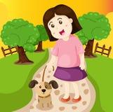 女孩走的狗在公园 免版税库存图片
