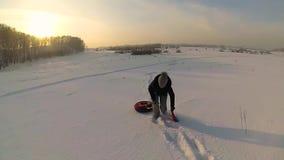 女孩起来到与snowtube的多雪的小山 慢的行动 雪冬天风景 风险轻率冒险日落时间 影视素材