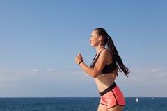 女孩跑体育和听到音乐 库存图片