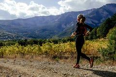 女孩跑在太阳谷葡萄园的赛跑者运动员 免版税库存照片