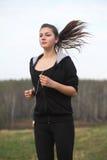 女孩跑步的公园年轻人 免版税库存图片