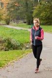 女孩跑步的公园 库存照片