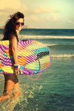 女孩跑的笑快乐获得与boogieboard的乐趣 免版税库存照片