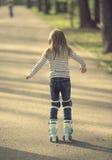 女孩路辗叶栅在公园,回到照相机 免版税库存图片