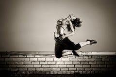 女孩跳的屋顶 免版税库存图片
