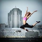女孩跳的屋顶 免版税库存照片