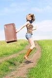 女孩跳的手提箱 库存照片