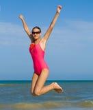 女孩跳的泳装 免版税库存图片