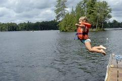 女孩跳的湖少许 免版税库存图片