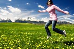 女孩跳的草甸年轻人 免版税库存图片