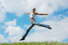 女孩跳的草甸 免版税图库摄影
