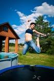 女孩跳绷床 免版税库存图片