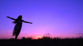 女孩跳舞剪影在桃红色日落的