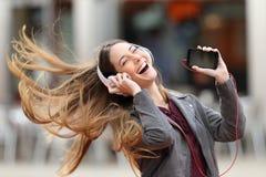 女孩跳舞和听的音乐在街道 免版税库存图片