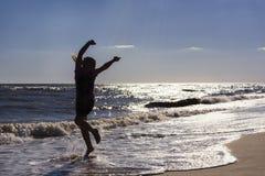 女孩跳舞和弹起在沿海岸区在日落的背景中 库存图片