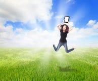 女孩跳草甸填充个人计算机显示接触 图库摄影