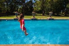 女孩跳跃的游泳池 图库摄影