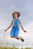女孩跳过少年的草绿色 免版税库存照片