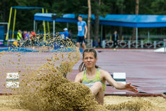 女孩跳远在竞争中 免版税库存照片
