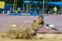 女孩跳远在竞争中 图库摄影