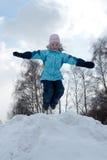 女孩跳随风飘飞的雪 免版税库存图片