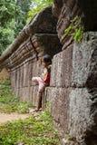 女孩身分对一个老石墙 免版税库存照片
