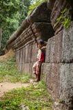 女孩身分对一个老石墙 免版税图库摄影