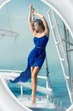 女孩身穿蓝服海游艇 库存照片