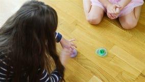 女孩转动蓝色和绿色锭床工人坐地板 股票视频