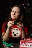 女孩转动绿色圣诞树由织品制成 图库摄影