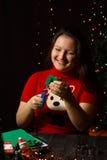 女孩转动绿色圣诞树由织品制成 库存图片