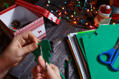 女孩转动绿色圣诞树由织品制成 免版税库存照片