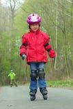 女孩轴向室外冰鞋滑冰 免版税库存图片