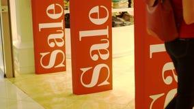 女孩输入的商店 在商店入口磁性门的三个销售标志 促销 消费者至上主义概念 股票录像