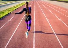 女孩运动员在体育场跑在日落 库存照片