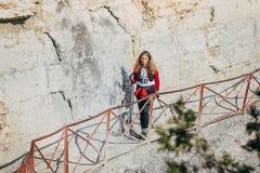 女孩运动员在沿峭壁岩石的足迹去 免版税库存图片