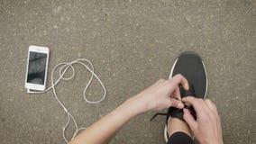 女孩运动员栓她的鞋带,当她的智能手机和耳机在地面时放置,通信概念 股票录像