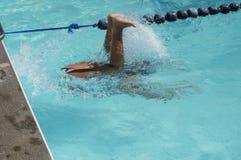 女孩运动员被训练为准备以后的每年游泳体育比赛翻滚轮在水面下 图库摄影