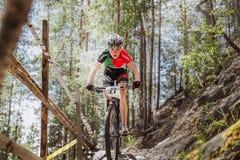 女孩运动员骑自行车者乘坐在山下一个木桥 免版税图库摄影