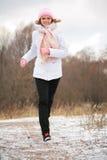 女孩运行冬天木年轻人 免版税库存照片